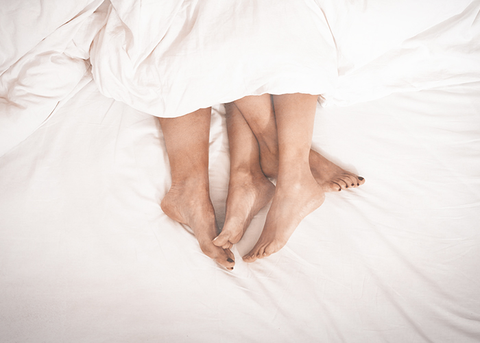 Feet of a couple lying in the bed